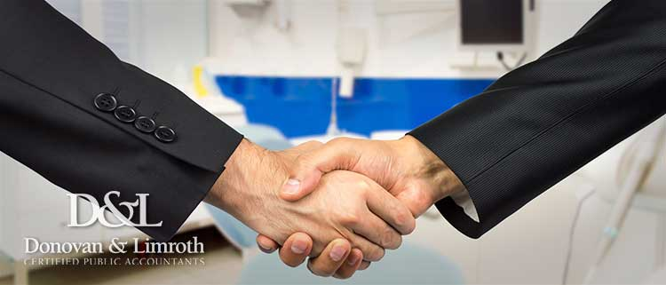 Business men shaking hands in dental office